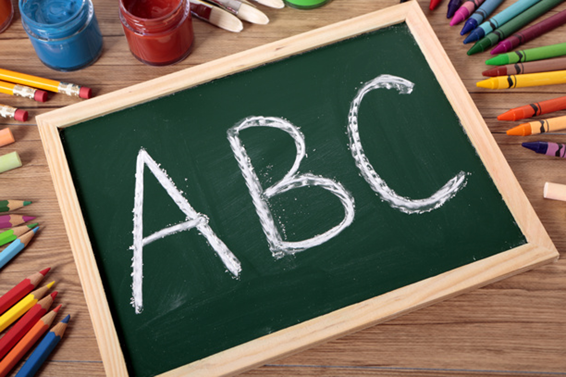 ABC written on a small elementary blackboard with various paints, crayons and pencils on a school desk.